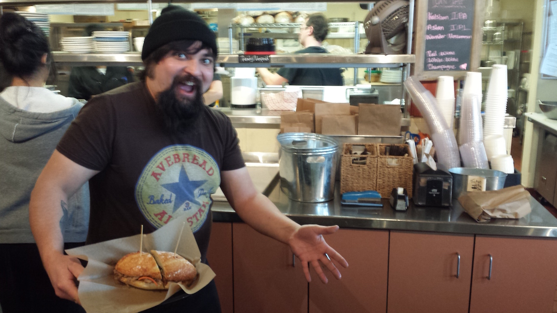 Avenue Bread employee holding sandwhich